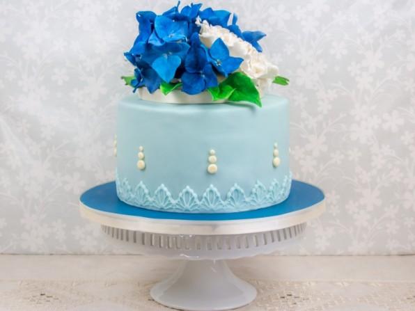 Torte mit blauen Hortensien und Pfingstrosen aus Zucker